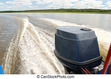 outboard motor boat on the river and wake