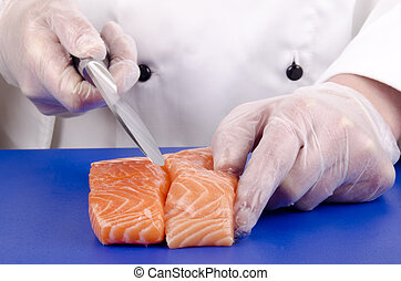 female chef cuts salmon fillets with a kitchen knife
