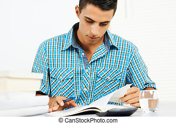 Young man reading and taking notes