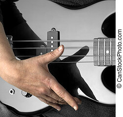 hand on bass guitar - female hand on the detail of a black...