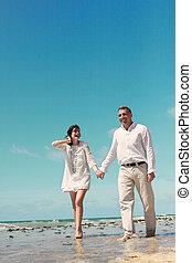 couple walking and laughing  in the sea coast
