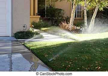 Sprinklers watering the grass and running onto the sidewalk...
