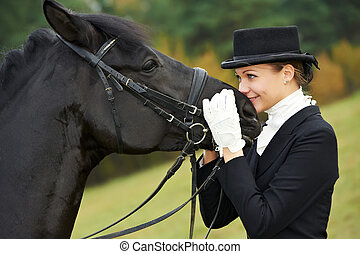 horsewoman jockey in uniform with horse