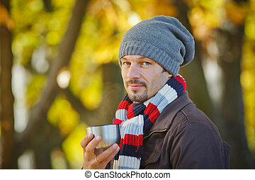 Man drinks tea in autumn park - Young happy man with scarf...