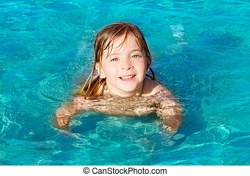 blond little girl swimming in turquoise beach