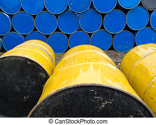 Stored stacks of colorful metal oil barrels - Yellow and...