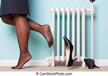 Woman kicking her heels off - Photo of a businesswomans legs...