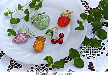 still life with jewelry fruits on white dish