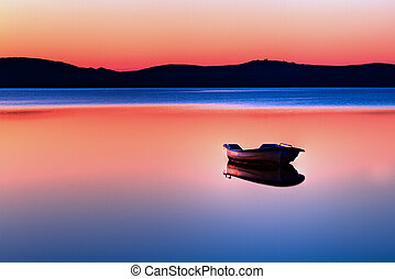 Boat in sunset - Scenic view of small fishing boat in calm...