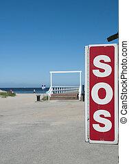 SOS phone on beach.