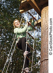 Canopy Adventure - Girl climbing rope ladder into tree...