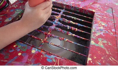 Kid making artwork with paints and a spinning disk