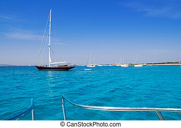 anchored sailboats in turquoise Formentera beach - anchored...