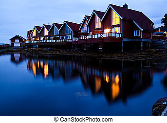 Camping cabins on a fjord at night - Red wooden cabins at...