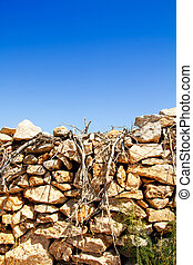 Mediterranean dried branches and masonry wall as Balearic...