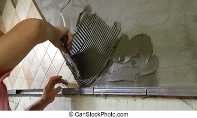 Installing Tile - Mans hands putting mortar on Kitchen wall,...