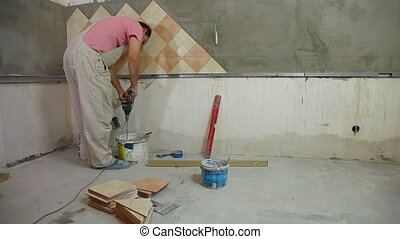 man installs ceramic tile - mixing grout, Wide Angle, Rear...