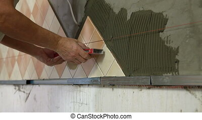 Worker installing Tiles - checking level Close-up