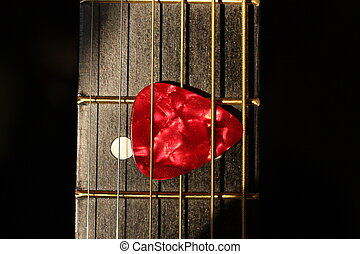 Red Pick - Photo of a red pick in the strings of a guitar