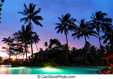 Sunset and illuminated swimming pool, Bentota, Sri Lanka