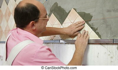 Man Tiling A Wall - man applying ceramic tile to a Kitchen...
