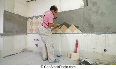 Worker installing Tiles to a Kitchen wall, Rear View, Wide...