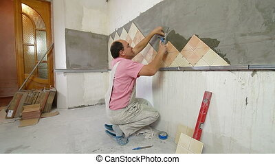 Worker installing Tiles to a Kitchen wall, Side View, Wide...