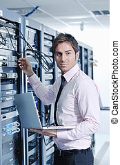 businessman with laptop in network server room - young...