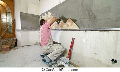 Man Tiling A Wall - Applying mortar to a Kitchen wall, Side...