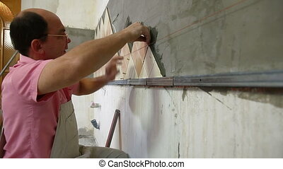 man applying ceramic tile to a Kitchen wall. Medium Shot,...