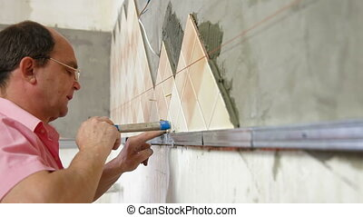 Worker installing Tiles - Man setting tile on cement board...