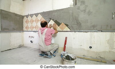 Worker installing Tiles to a Kitchen wall, Wide Angle