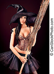 horror - Charming halloween witch with broom over black...