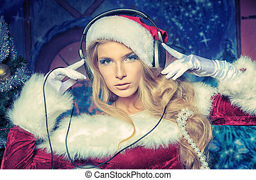 xmas dj - Beautiful young woman in Santa Claus clothes and...