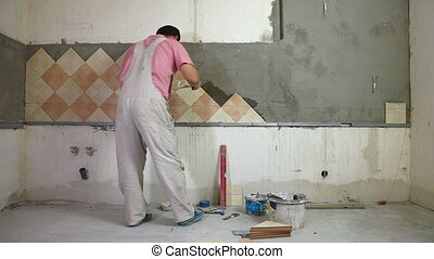 Tile work - man applying ceramic tile to a Kitchen wall,...