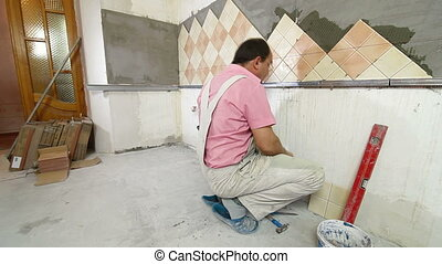 Setting Tile - Man setting tile on cement board in the...