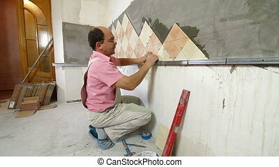 man applying ceramic tile - Man setting tile on cement board...