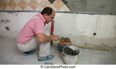 applying mortar to ceramic tile - Man show applying mortar...