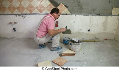 putting mortar on Tiles - man applying ceramic tile to a...