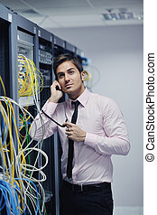 it engineer talking by phone at network room