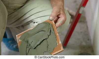 putting mortar on Tile - Mans hands show applying mortar to...