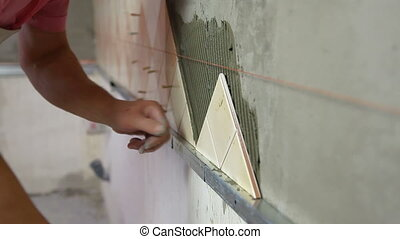 Installing Tiles - checking level - man applying ceramic...