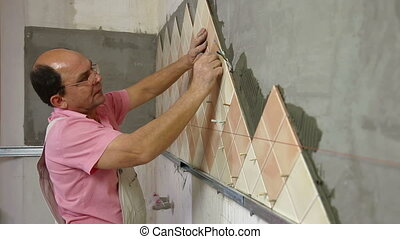 Man applying ceramic tile to a Kitchen wall, Side View,...