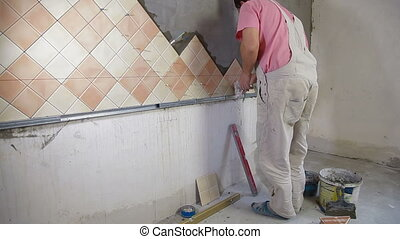 Man Tiling A Wall - Man setting tile on cement board, Side...