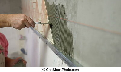 Installing Ceramic Tile - Man's hands Installing Ceramic...