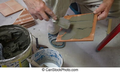 putting mortar on Tile - Man's hands show applying mortar to...