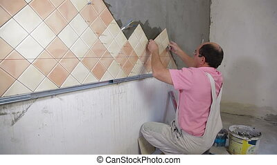 Kitchen Tile - Man setting tile on cement board, Side View,...