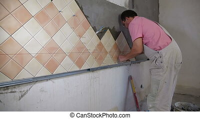Installing Ceramic Tile - Man setting tile on cement board,...