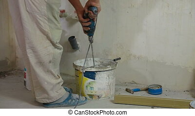 Installing Tiles - man installs ceramic tile - mixing grout