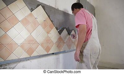 Installing Tiles - Applying mortar - man applying ceramic...
